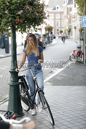 netherlands maastricht young woman with bicycle