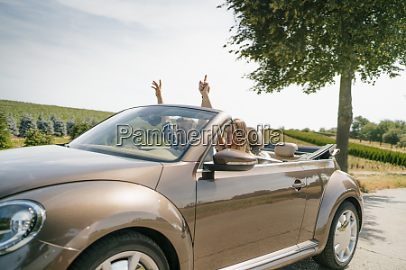 happy couple driving in convertible car