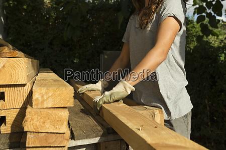 handwerkerin traegt schutzhandschuhe die mit holz