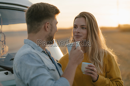 smiling young couple holding mugs at