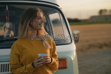 happy young woman holding mug at