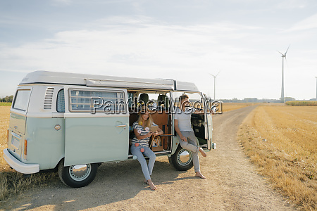 young couple relaxing in camper van