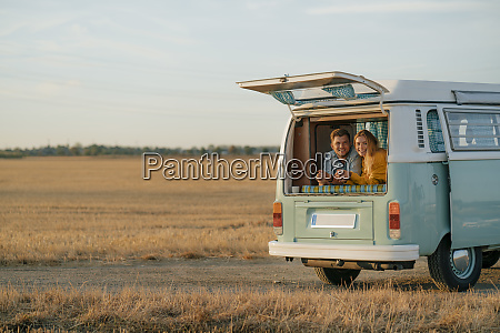 happy young couple lying in camper