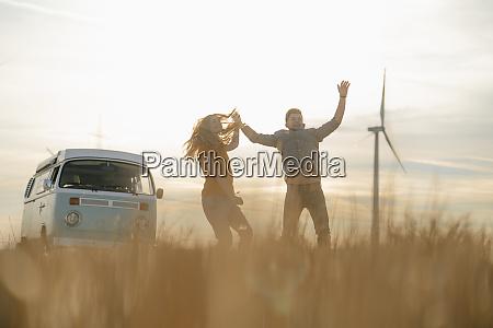 exuberant couple at camper van in