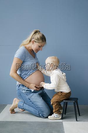 kleinkindsohn untersucht bauch auf schwangeren mutter