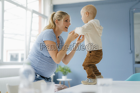 happy pregnant mother with toddler son