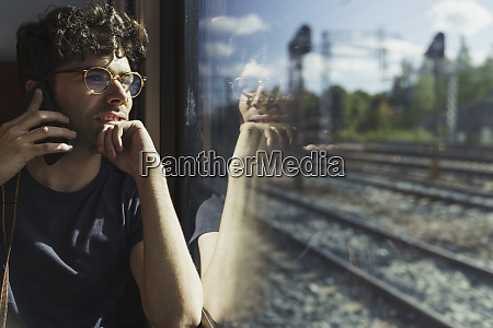 man traveling by train talking on