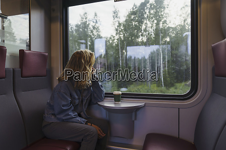 woman traveling by train looking out