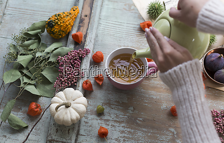 womans hands pouring tea in a