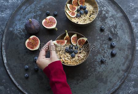 womans hand garnishing bowl of porridge