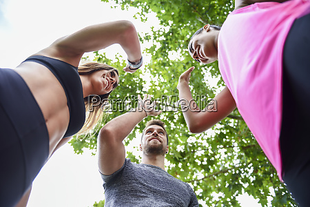 junge sportmannschaft hochfiffend im park feiert