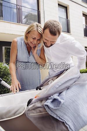 happy couple looking into pram