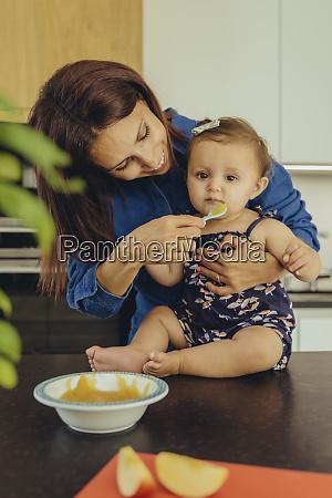 mother helping baby daughter eating fruit