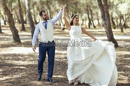 glueckliches brautpaar tanzt zusammen im pinienwald