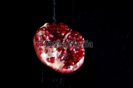 sliced pomegranate in front of black