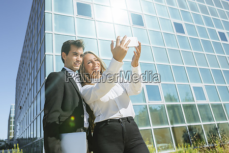 smiling businesswoman and businessman taking a