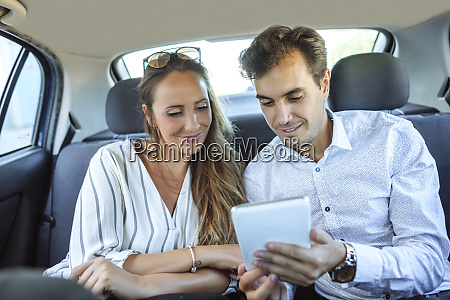 couple using tablet on back seat