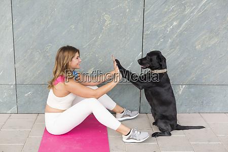 junge frau sitzt auf yoga matte