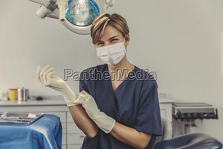 dental surgeon wearing surgical mask putting