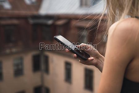 frau haelt smartphone nahaufnahme