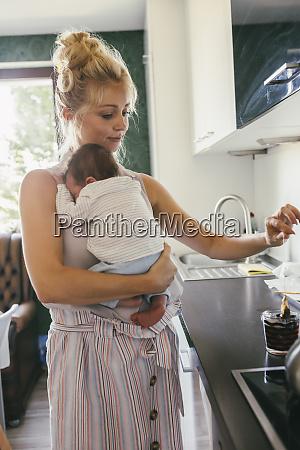 mother holding newborn baby in kitchen