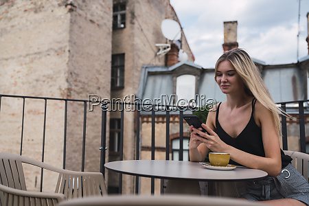 smiling blond woman sitting on roof