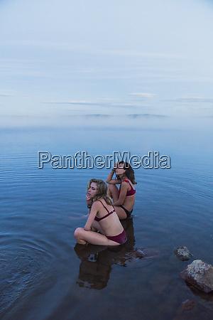 two young women wearing bikinis sitting