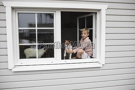 portrait of boy sitting on window