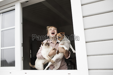 boy standing at open window with