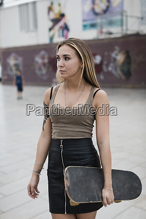 cool young woman carrying skateboard in