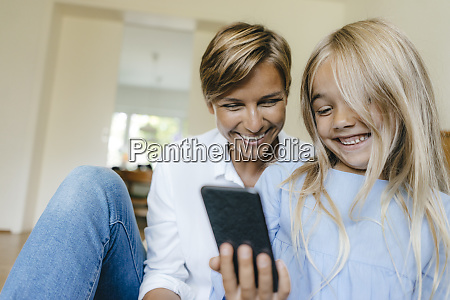 happy mother and daughter looking at