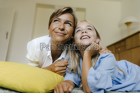 happy mother and daughter lying on