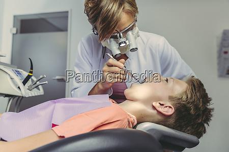 denist examining boys teeth using head