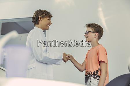 boy greeting dentist shaking hands