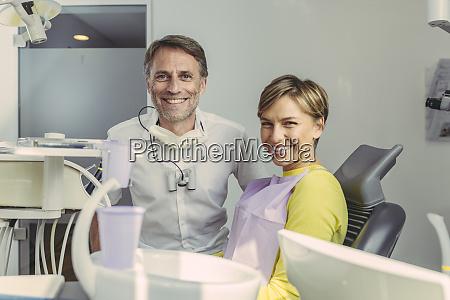 zahnarzt und patient laechelnd an kamera