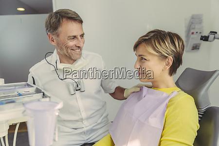 zahnarzt beruhigt seinen patienten vor der