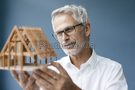 successful architect looking at model of