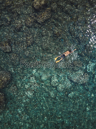 indonesia bali man swimming in ocean