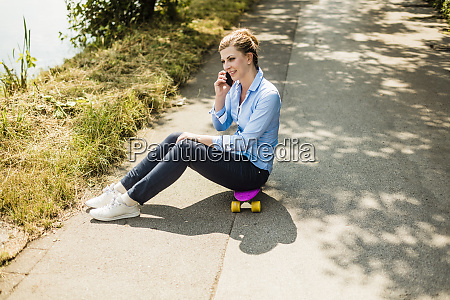 smiling woman sitting on penny board