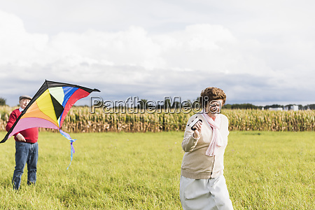 senior couple flying kite in rural