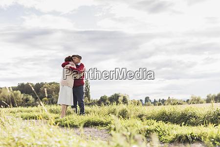 senior couple hugging in rural landscape