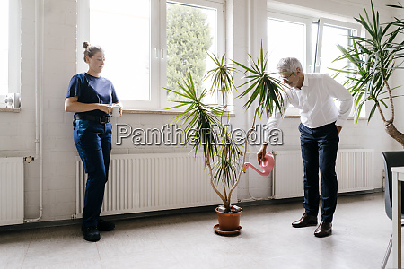 manager watering plants in recreation room