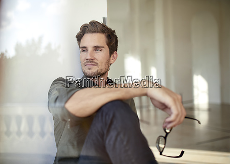 portrait of content young businessman looking