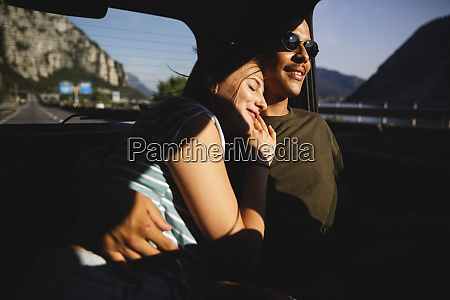 smiling affectionate young couple sitting on