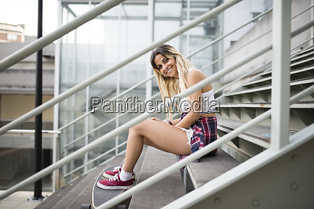 young woman with long board sitting
