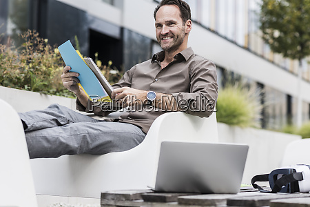 smiling businessman with document laptop and