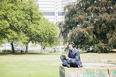 geschaeftsmann im stadtpark mit kopfhoerern und