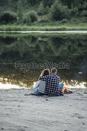 romantic couple sitting at the riverside