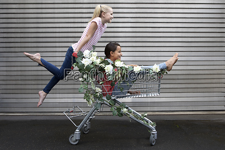 two girls playing with shopping cart