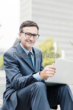 portrait of smiling businessman sitting down